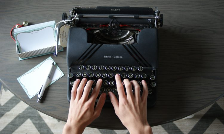 man's hands typing on a smith corona